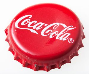 MOSCOW RUSSIA - DECEMBER 12 2105: Used red cap from the glass bottle of Coca-Cola. The Coca-Cola Company is an American beverage corporation and manufacturer founded in 1886.